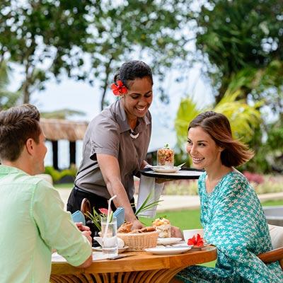 couple being served fijian cuisine